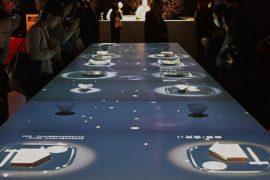 「食べるアート展 L'art de Rosanjin」のイベント会場に設置された 「季節の食卓プロジェクション」。テーブル上に置かれたさまざまな空の食器に、季節の料理が出現して彩られていきます。
