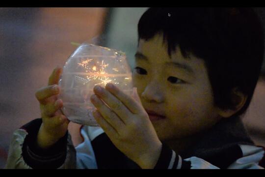 ガラスポットの中の線香花火「手のひら花火」を見つめる、男の子。